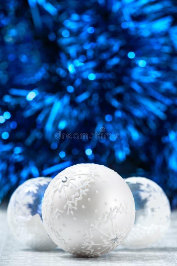 Vit- och silverjulbollar på mörker - blå bokehbakgrund med utrymme för text Glad julkort nytt år royaltyfria foton