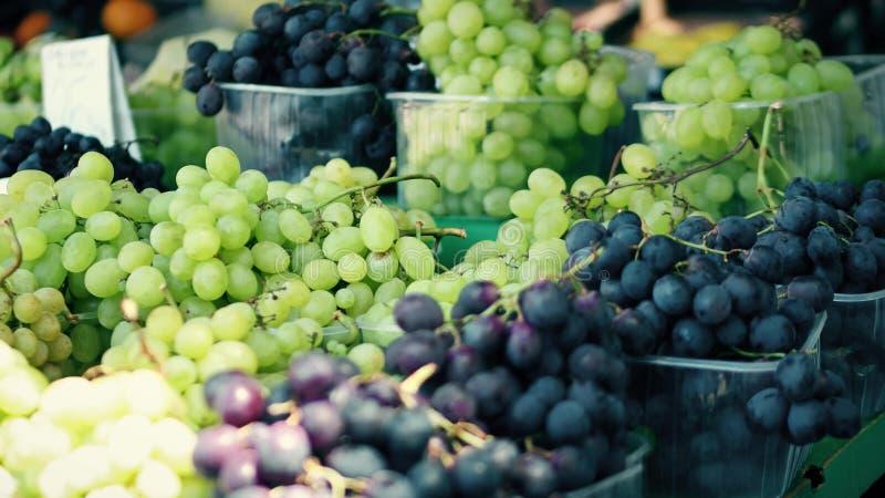 Vit- och svartdruvor stannar på den lokala bondemarknaden arkivbilder