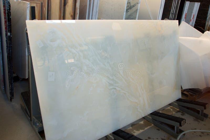 Vit onyx står på en kugge i ett lager med stenar royaltyfri fotografi