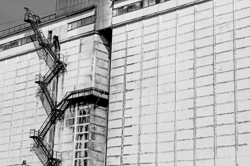 Vit påfyllning-lager vägg av en stor industribyggnad med stöd och en brandmetallstege i bakgrunden Svart bakgrund och royaltyfria bilder