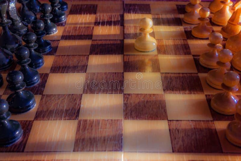 Vit pantsätter att bli mot den fulla uppsättningen av svarta schackstycken Closeup av schackbr?det med tr?stycken p? tabellen i s arkivfoton