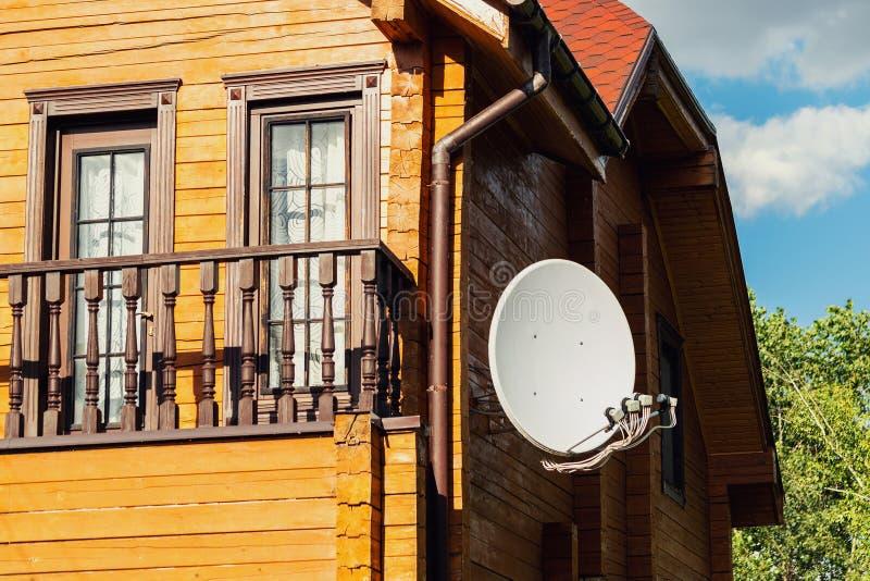 Vit parabolisk satellit- antenamaträtt som hängs på väggen av den moderna trävillan för landshus Trådlös television royaltyfria foton