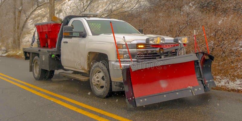 Vit pickup som reser på en väg längs ett snöig berg i vinter royaltyfria foton