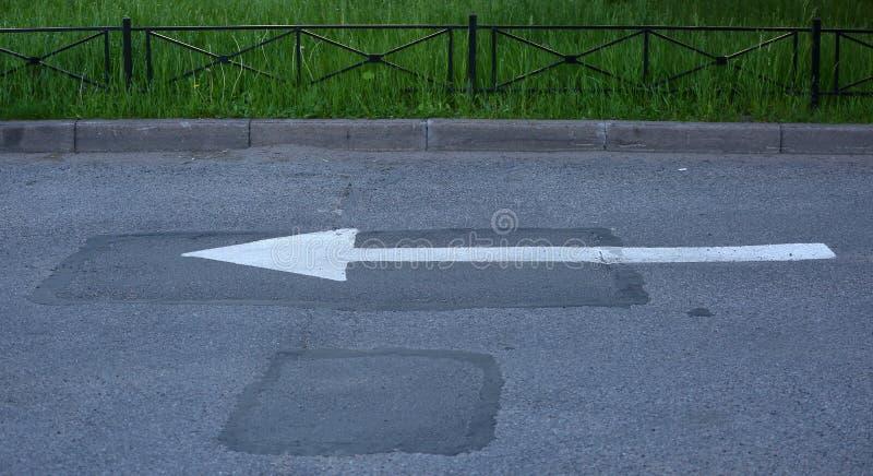 Vit pil på asfaltvägen, symbolet av riktningen av rörelse arkivbild