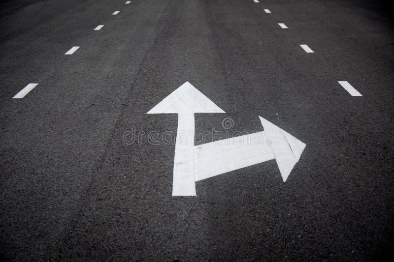Vit pilraksträcka framåt eller högert perspektiv för vändtrafiktecken på vägen arkivfoto