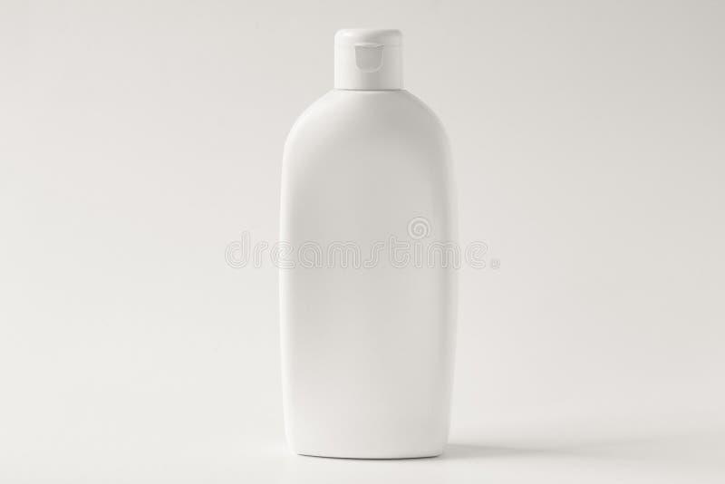 Vit plast- flaska för kräm på en vit bakgrund Bekläda beskådar arkivbilder