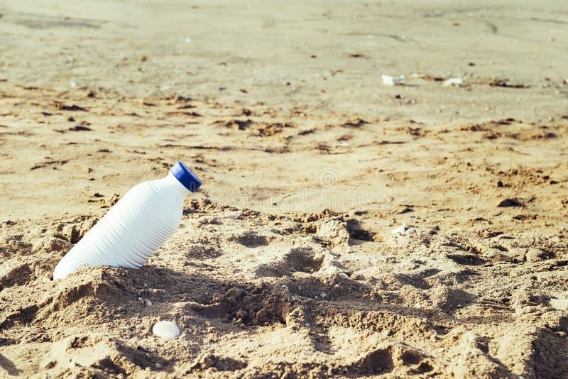 Vit plast- flaska som ligger på strandsanden arkivfoton