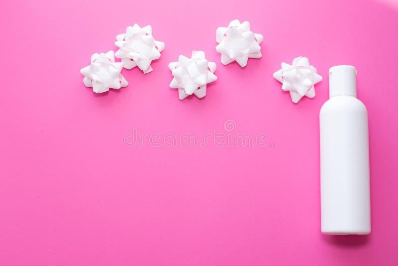 Vit plast- flasksprej med små blommor på en rosa bakgrund Hud kroppomsorg placera text arkivbilder