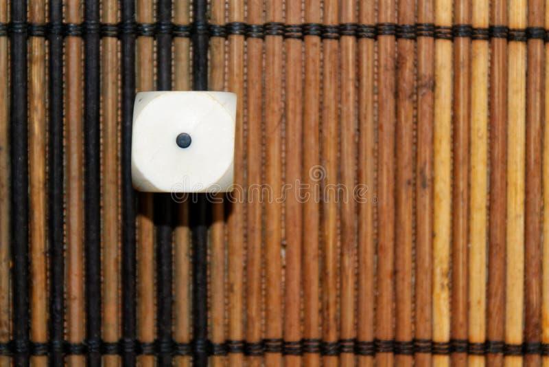 Vit plast- tärning en på brun träbrädebakgrund Sex sidokub med svarta prickar Nummer 1 royaltyfri bild