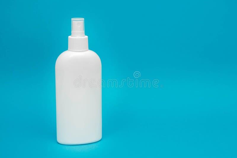 Vit plastflaska för sprutning av flytande kosmetika mot blå bakgrund Spa-koncept Kopiera, tomt utrymme för text royaltyfria bilder