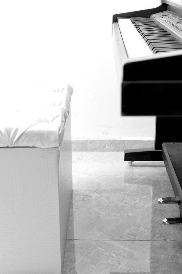 Vit plats med det svarta pianot och vit vägg royaltyfri bild