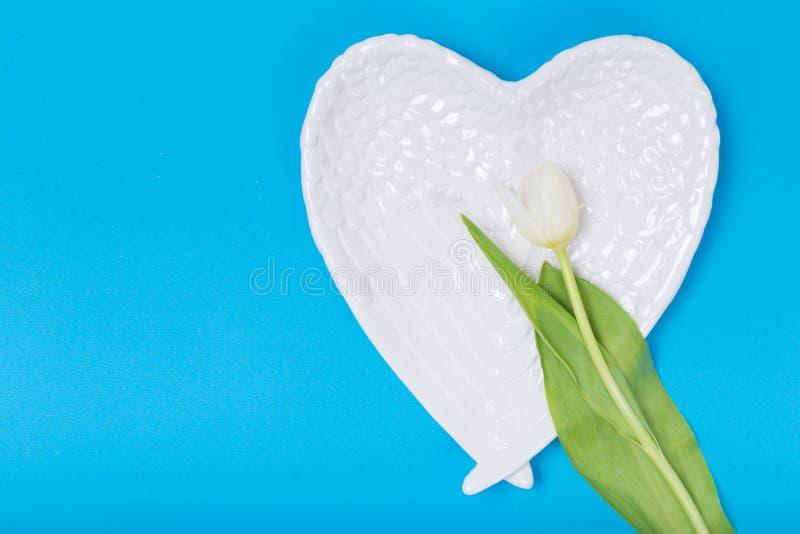 Vit platta för hjärtaform på blå bakgrund fotografering för bildbyråer