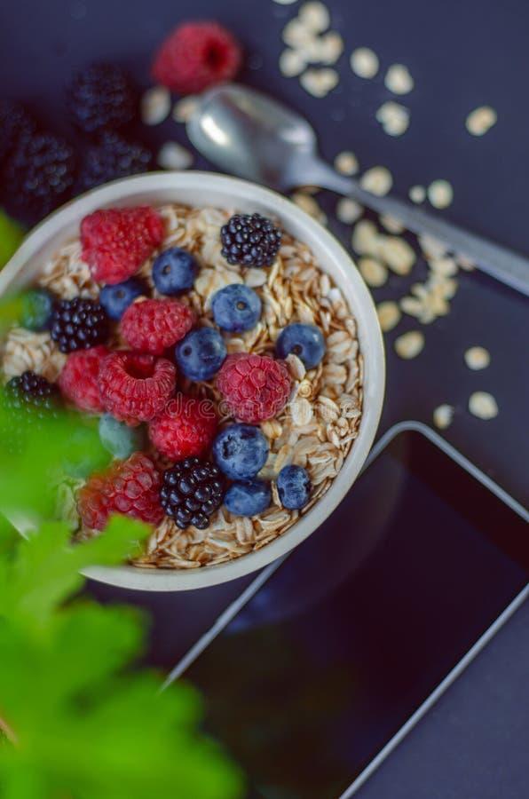 Vit platta för sund frukost med beströdde och olika bär för havremjöl på en blå bakgrund Sommarskörd royaltyfria bilder