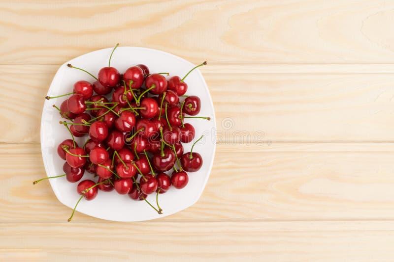 Vit platta mycket av mogna körsbär på den bästa sikten för tabell royaltyfria foton
