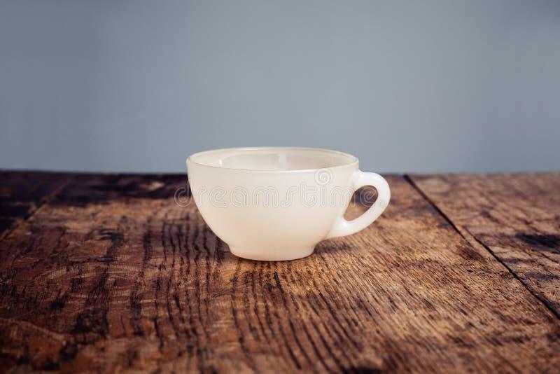 Vit porslinkaffekopp på en wood tabell royaltyfri fotografi