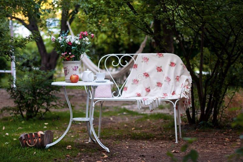 Vit porslinuppsättning för te eller kaffe på tabellen i trädgården över bakgrund för suddighetsgräsplannatur Utomhus- parti för s arkivfoton