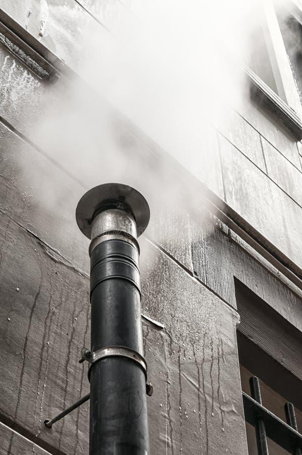 Vit rök som kommer ut ur ett stålrör fotografering för bildbyråer