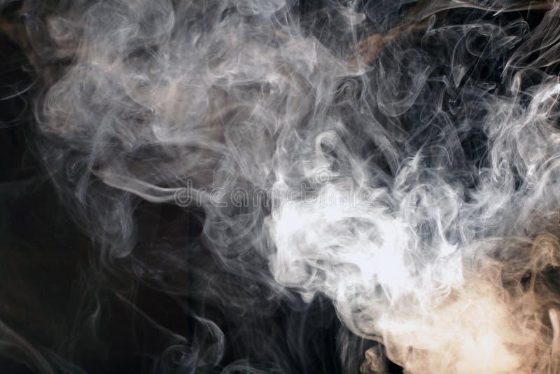 Vit rökfläck på svart arkivbild