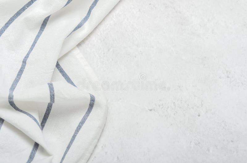 Vit ren handduk på ett ljust - grå färgstenbakgrund Minimalist kök arkivfoton