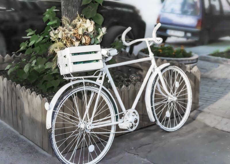 Vit retro cykel med träasken med blommor på stadsgatan arkivfoto