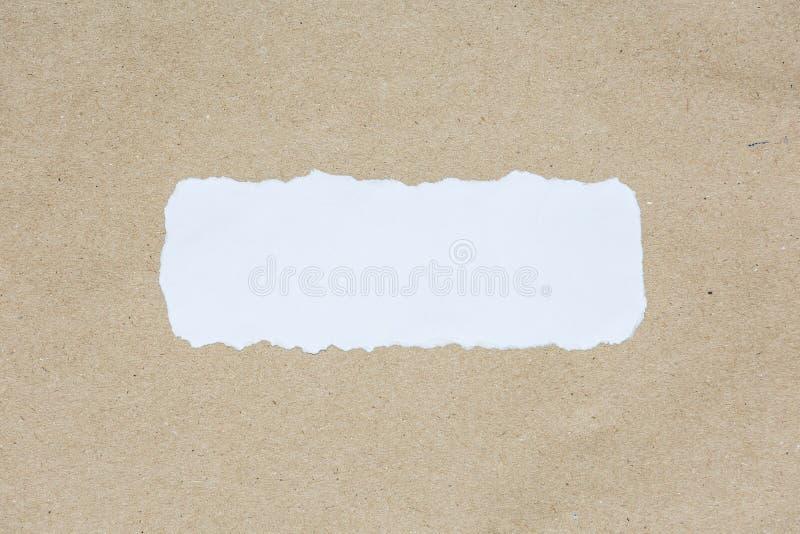 Vit rev sönder stycket av papper på brunt dokumenttexturpapper royaltyfri fotografi