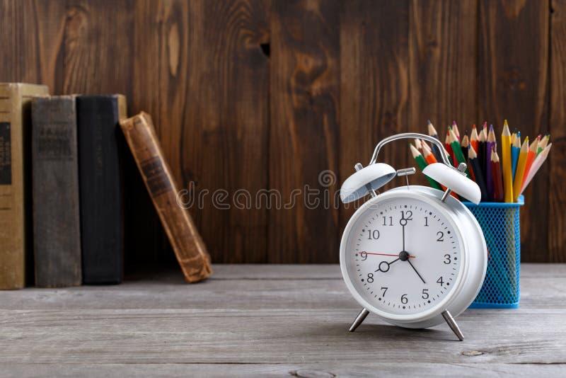 Vit ringklocka med gamla böcker och färgade blyertspennor royaltyfria foton