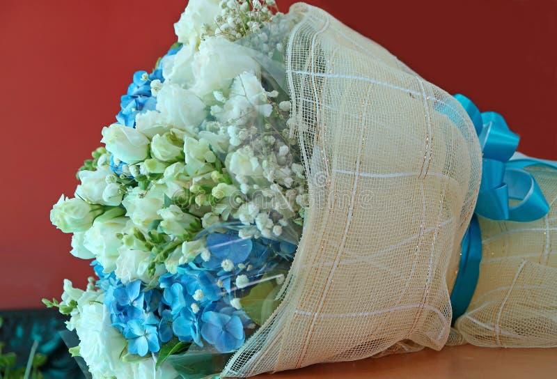 Vit ros och blå vanlig hortensiabukett på tabellen royaltyfria foton