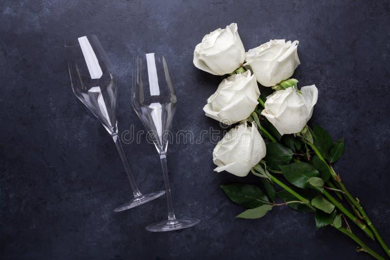 Vit rosa blommabukett, champagneexponeringsglas på svart kort för hälsning för stenbakgrundsromantiker royaltyfri bild