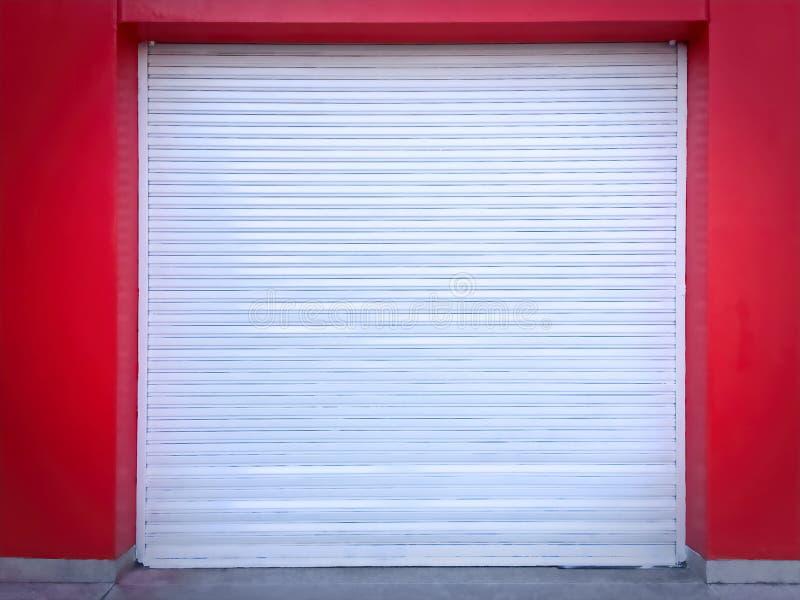 Vit rull-uppdörr på den röda väggen av garaget fotografering för bildbyråer
