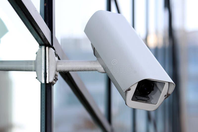 Vit säkerhetscctv-kamera på den glass fasaden arkivbilder