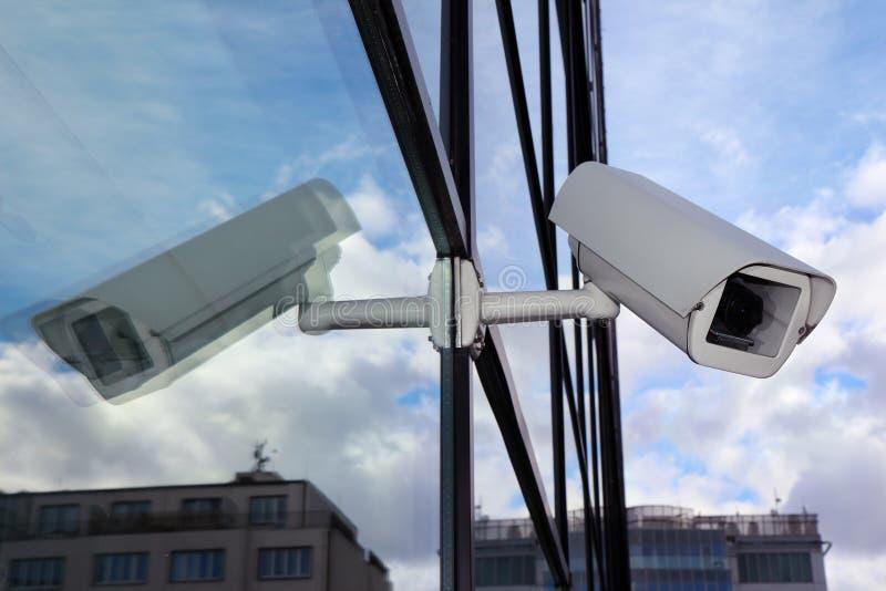 Vit säkerhetscctv-kamera på glasväggen arkivfoton