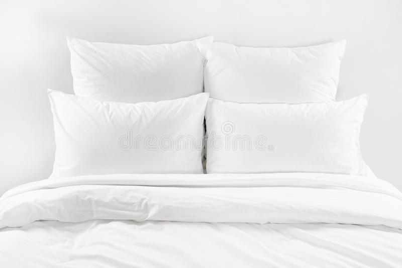 Vit säng, fyra vita kuddar och duntäcke på en säng royaltyfria bilder