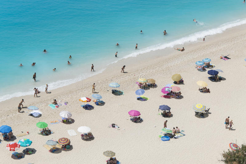 Vit sandÂstrand med färgrika slags solskydd arkivbilder