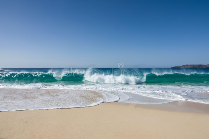 Vit sand av en härlig strand och vågor av ett turkoshav under en blå himmel arkivfoto