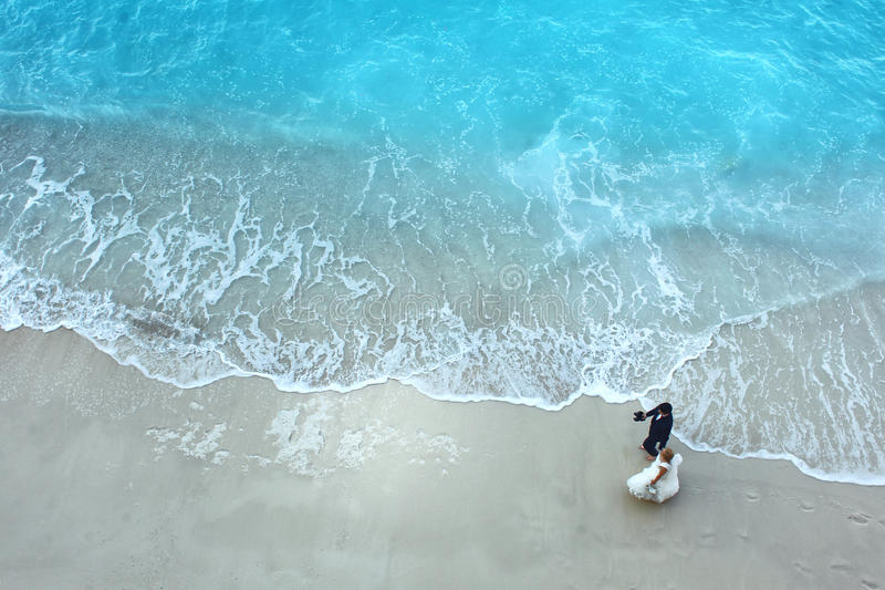 Vit sandstrand och blått vatten med härliga älskvärda par för brud och för brudgum royaltyfri bild