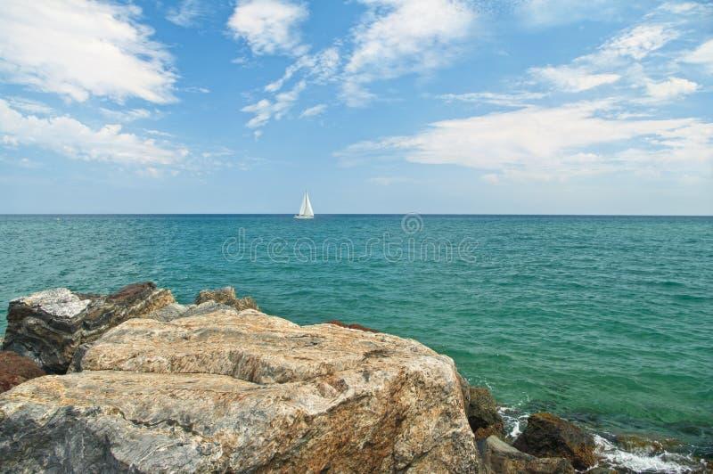 Vit segelbåt på horisont i havet från stenig kust royaltyfri foto