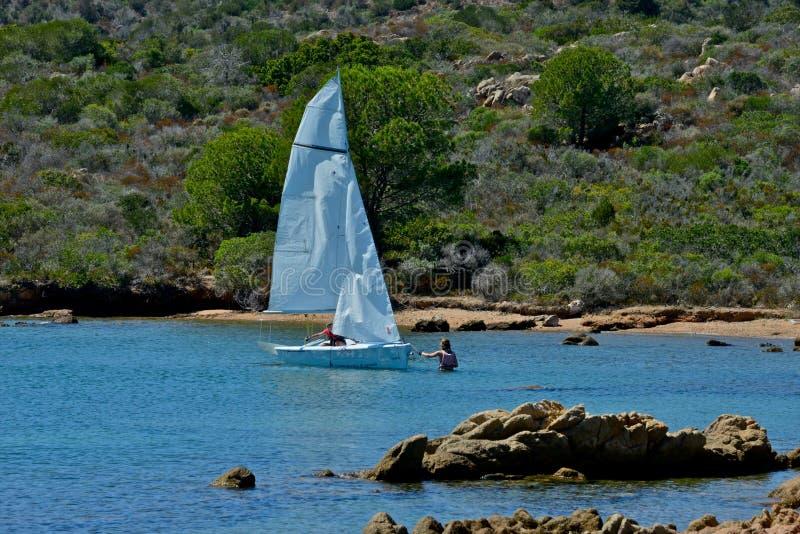 Vit seglar fartyg med två personer som lär att segla i det blåa havet som av naturen omges arkivbild