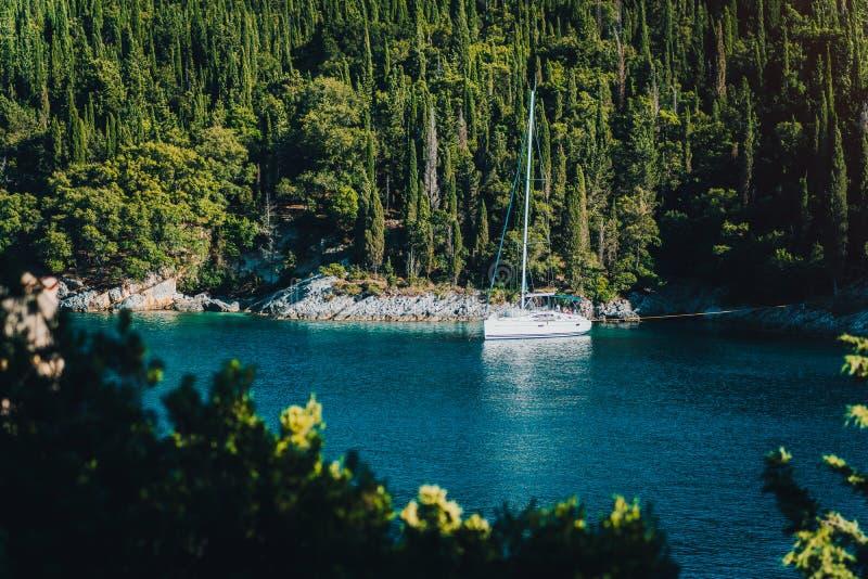 Vit seglar fartygyachten som förtöjas i fjärden av den Foki stranden med cypressträd i bakgrund, Fiskardo, Cefalonia som är ionia arkivbilder