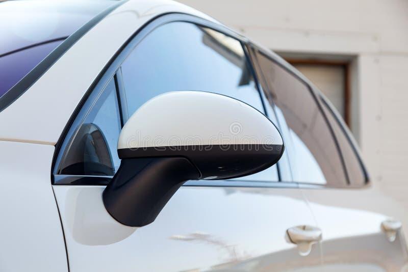 Vit sikt för spegel och för fönster för främre sida för bilår med ID-Märkediesel i utmärkt villkor i en parkeringsplats bland and arkivbilder