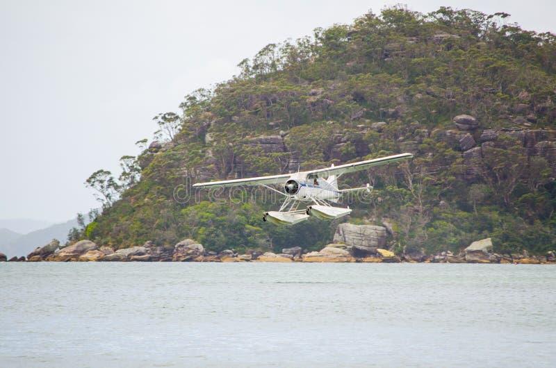 Vit sjöflygplan som tar av från havyttersida med bergsikt i bakgrunden på Palm Beach, Sydney, Australien arkivbilder