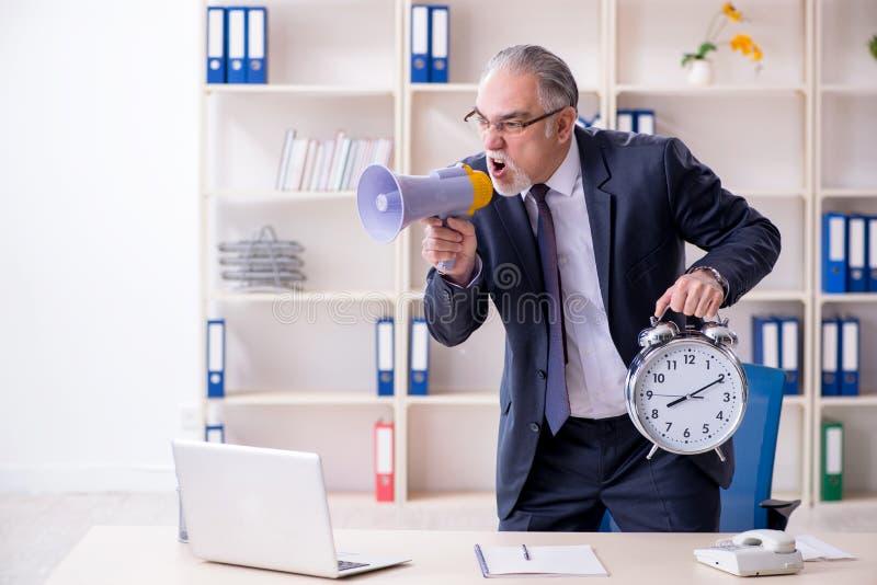 Vit skäggig gammal affärsmananställd som är olycklig med överdrivet arbete arkivfoton