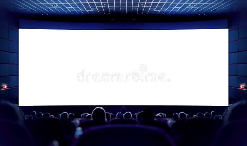 Vit skärm i bion och åhörarna som håller ögonen på filmen bio royaltyfri bild