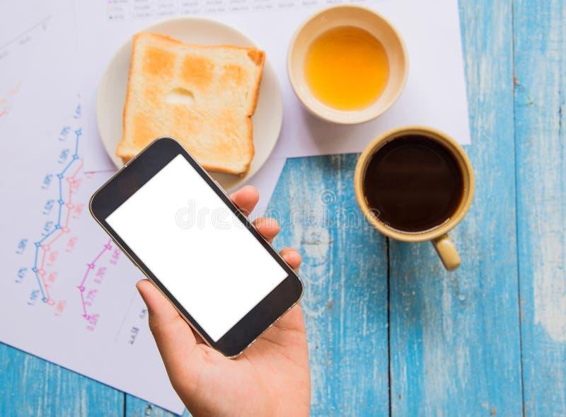 Vit skärmSmart telefon i handen, rostat bröd, honung, kaffekopp royaltyfri foto