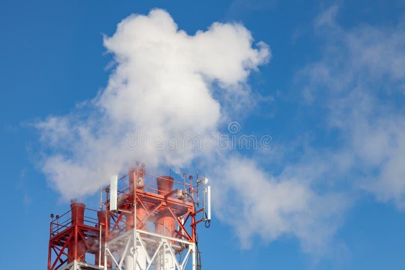 Vit skadlig r?k som kommer ut ur devit r?ren med antenner f?r mobil kommunikation p? en fabrik i centret arkivfoto