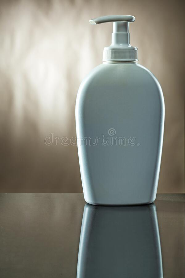 Vit skinksprutare för flaska med kräm på spegel arkivfoto
