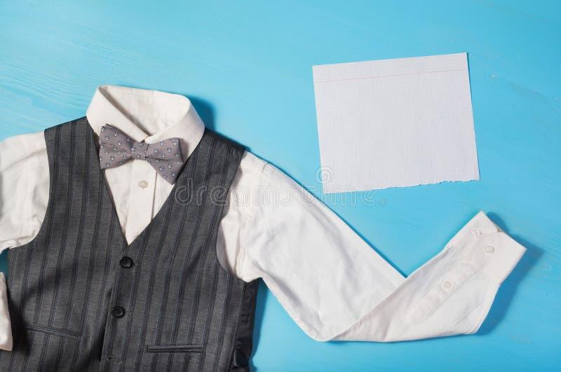 Vit skjorta, grå väst och en fluga på en ljus blå bakgrund royaltyfri fotografi