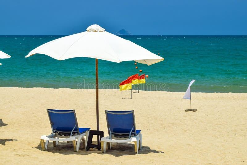 Vit slags solskydd med två stolar på stranden nära havet på solig dag arkivbild