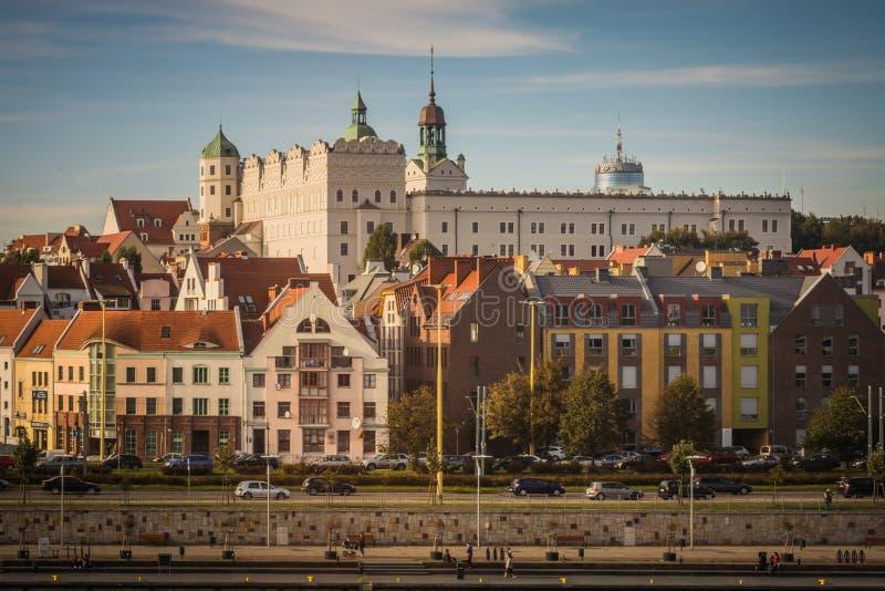 Vit slott med torn och gräsplantak och röda tak av bostads- och den kontorshus och vägen i Szczecin, Polen arkivbilder