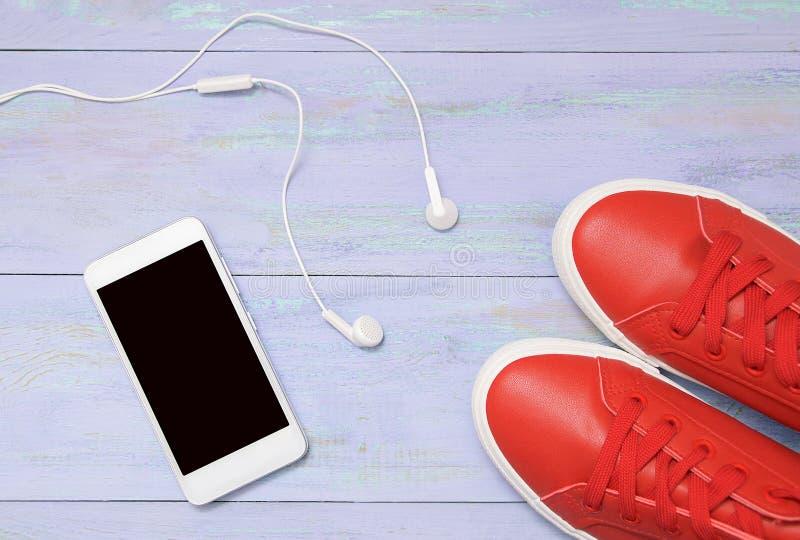 Vit smartphone, hörlurar och röda gymnastikskor På violett träbakgrund royaltyfria foton