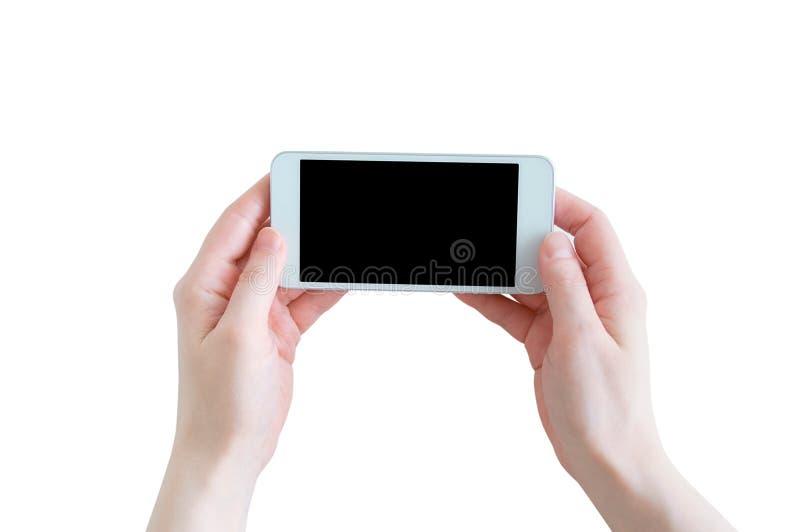 Vit smartphone med svarta skärmhänder av den Caucasian flickan royaltyfri foto